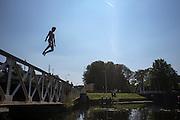 Een jongen springt vanaf de Muntbrug in Utrecht het verkoelende water van het Merwedekanaal in. Op waarschijnlijk de laatste mooie zomerse dag genieten mensen nog volop van de zon.<br /> <br /> Young people are jumping of a bridge in Utrecht into the cool water of the Merwedekanaal.