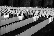 Verdun WW1 Battlefield site, Verdun-sur-Meuse, France. March 2014<br /> Seen here : At dusk Muslim man visits  the section of the cemetery where Muslims who died for France fighting in the Battle for Verdun lie buried.<br /> The French Cemetery and the Great Ossuary at Douaumont. 16,143 lie dead in the cemetery, all identified except for 540 buried in plot 1. The Ossuary contains the bones of over 130,000 soldiers, both French and German all unidentified.<br /> <br /> The Battle of Verdun lasted 9 months, 3 weeks and 6 days between 21 February and 20 december 1916. It was the longest and one of the most costly battles in human history;  recent estimates increase the number of casualties to 976,000.<br /> <br /> Caption information below from wikipedia:<br /> The Battle of Verdun (Bataille de Verdun), was fought from 21 February – 18 December 1916 during the First World War on the Western Front between the German and French armies, on hills north of Verdun-sur-Meuse in north-eastern France. The German Fifth Army attacked the defences of the Région Fortifiée de Verdun (RFV) and the Second Army on the right bank of the Meuse, intending rapidly to capture the Côtes de Meuse (Meuse Heights) from which Verdun could be overlooked and bombarded with observed artillery-fire. The German strategy intended to provoke the French into counter-attacks and counter-offensives to drive the Germans off the heights, which would be relatively easy to repel with massed artillery-fire from the large number of medium, heavy and super-heavy guns, supplied with large amounts of ammunition on excellent pre-war railways, which ran within 24 kilometres (15 mi) of the front-line.<br /> <br /> The German strategy assumed that the French would attempt to hold onto the east bank of the Meuse, then commit the French strategic reserve to recapture it and suffer catastrophic losses from German artillery-fire, while the German infantry held positions easy to defend and suffered few losses. The German p