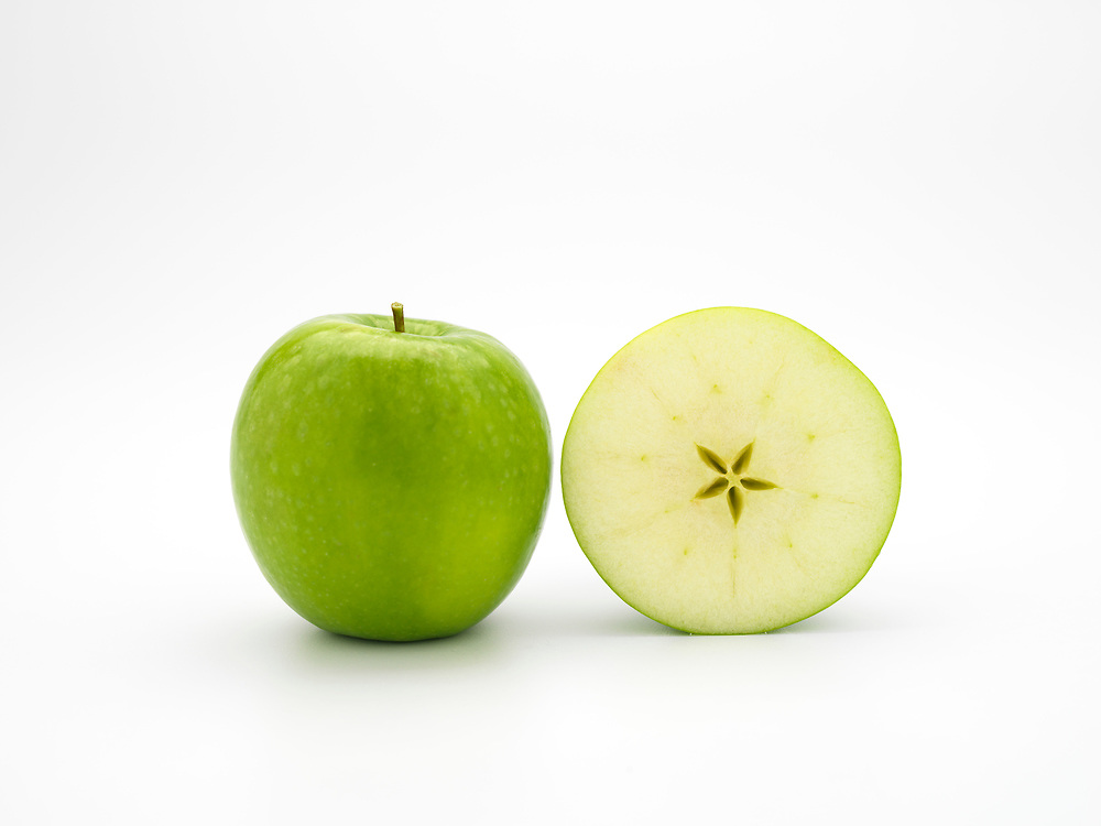 Whole green apple and an apple slice on a white background