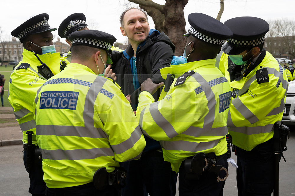 © Licensed to London News Pictures. 06/03/2021. London, UK. A protester is arrested by police officers at an anti-vaccination and anti-lockdown demonstration organised by Jam For Freedom in Richmond. The group is using music to create positive effects and health against the current tier regulations and anti-vaccination for the Covid-19 disease. Photo credit: Ray Tang/LNP