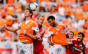 Apr 14, 2013; Houston, TX, USA; Houston Dynamo defender Bobby Boswell (32) heads a ball against Chicago Fire midfielder Jeff Larentowicz (20) in the first half at BBVA Compass Stadium. Mandatory Credit: Thomas Campbell-USA TODAY Sports