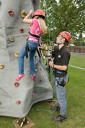 Adventure activities instructor teaching a girl how to use the climbing wall at a Parklife summer activities event,
