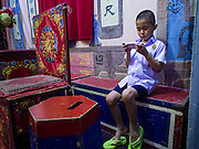 "30 JUNE 2016 - BANGKOK, THAILAND:  A boy whose parents are performers in a Chinese opera troupe does his homework before an opera performance at Chiao Eng Piao Shrine in Bangkok. Chinese opera was once very popular in Thailand, where it is called ""Ngiew."" It is usually performed in the Teochew language. Millions of Chinese emigrated to Thailand (then Siam) in the 18th and 19th centuries and brought their culture with them. Recently the popularity of ngiew has faded as people turn to performances of opera on DVD or movies. There are about 30 Chinese opera troupes left in Bangkok and its environs. They are especially busy during Chinese New Year and Chinese holidays when they travel from Chinese temple to Chinese temple performing on stages they put up in streets near the temple, sometimes sleeping on hammocks they sling under their stage.      PHOTO BY JACK KURTZ"