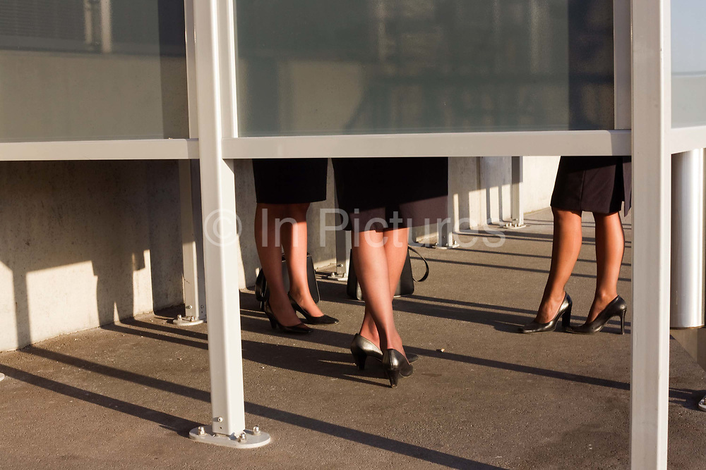 """The legs of anonymous airline employees are seen from below a smoking screen that obscures their faces outside Heathrow Airport's Terminal 5 building. In afternoon sunshine, the women wear their airline uniforms and are sharing an off-duty puff on their cigarettes as part of their working shift at this international aviation hub. Without seeing their upper-bodies, we imagine their conversation and gossip. From writer Alain de Botton's book project """"A Week at the Airport: A Heathrow Diary"""" (2009)."""