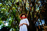 A young Vietnamese woman wearing an ao dai and a conical hat in southern Vietnam.