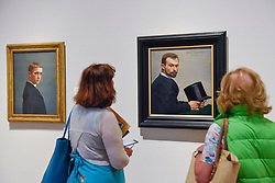 """© Licensed to London News Pictures. 27/06/2019. LONDON, UK. Visitors view (L) """"Self-portrait at the Age of Twenty (Autoportrait à l'âge de vingt ans)"""", 1885, and (R) """"Félix Jasinki Holding His Hat (Félix Jasinki tenant son chapeau)"""", 1887, both by Félix Vallotton. Preview of """"Félix Vallotton:  Painter of Disquiet"""", an exhibition of paintings and prints Swiss artist Félix Vallotton at the Royal Academy of Arts.  Around 100 works are on show 30 June to 29 September 2019.   Photo credit: Stephen Chung/LNP"""