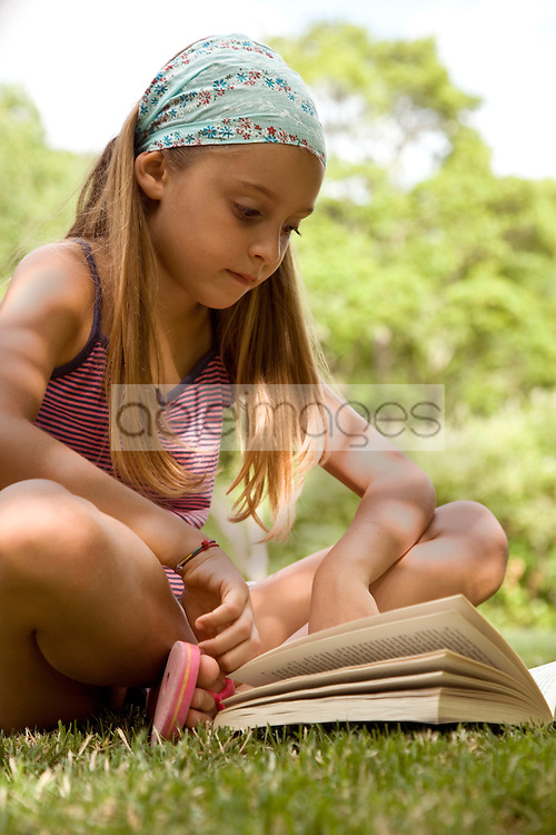 Portrait of young girl sitting cross legged reading book