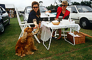 In a grass-covered car park, two ladies sit on garden chairs adorned with white table cloth. One pours champagne into a glass flute while her girlfriend reaches down to her beloved pet spaniel dog that eagerly licks at a fresh strawberry. The ladies are attending an international polo match between Great Britain and the USA in Windsor Great Park, near Windsor Castle, one of the Queen's official residences. There is a wicker picnic hamper on the grass too, probably containing the couples' lunch. The day is overcast, with threatening clouds behind the party but despite this, they are in a bubbly and excitable mood. Polo at Windsor is held annually and is one of the main dates on the sporting calendar and social season.