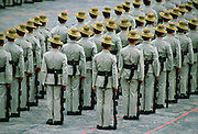 Ranks of Gurkha soldiers standing in lines with their traditional Kukri knives attached to scabbards on their belts and their rifles at their sides, Hong Kong