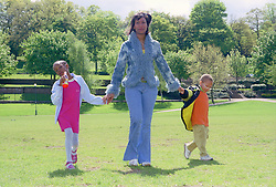 Single mother walking across park holding hands of young daughter and son,