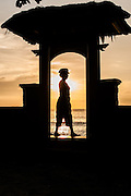 Woman silhouette through gate at sunset