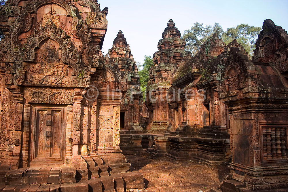 """Banteay Srei. This beautiful and intricately carved, fine grained rose coloured sandstone temple is situated 30km north of Siem Reap. This is the most intricately carved of all of Angkor's temples, with it's surfaces depicting floral designs and """"Ramayana"""" scenes. It is a small and compact temple, whose stunning carvings make for one of Angkor's most intriguing."""