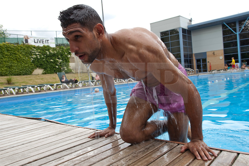 "© Licensed to London News Pictures. 30/05/2012. Bolton, UK. Amir Khan holds a workout photocall in Bolton ahead of his stint as an Olympic torchbearer on 31st May. He emerges from a swimming pool with a sign reading ""Live it"" in the background. Photo credit : Joel Goodman/LNP"