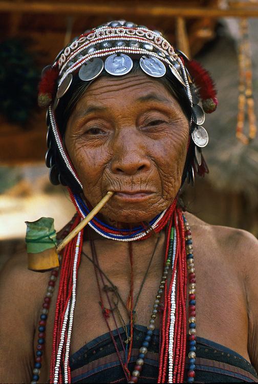 Akha tribeswoman smoking a bamboo pipe, village near Chiang Mai, Thailand.   1988