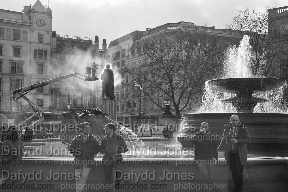 Winston Bogle of DBR Conservation maintenance cleaning statue in Trafalgar Sq. London. . 7 March 2018