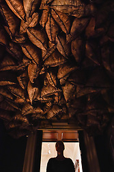 """© Licensed to London News Pictures. 03/10/2017. London, UK.  A staff member, seen in silhouette, views a reconstruction of """"Twelve Hundred Coal Sacks Suspended From The Ceiling Over A Stove"""", 1938, by Michel Duchamp at the preview of """"Dali / Duchamp"""", a new exhibition of works by Salvador Dali and Michel Duchamp taking place at the Royal Academy of Arts in Piccadilly.  Over 80 artworks in different media are on display from 7 October to 3 January 2018.   Photo credit : Stephen Chung/LNP"""