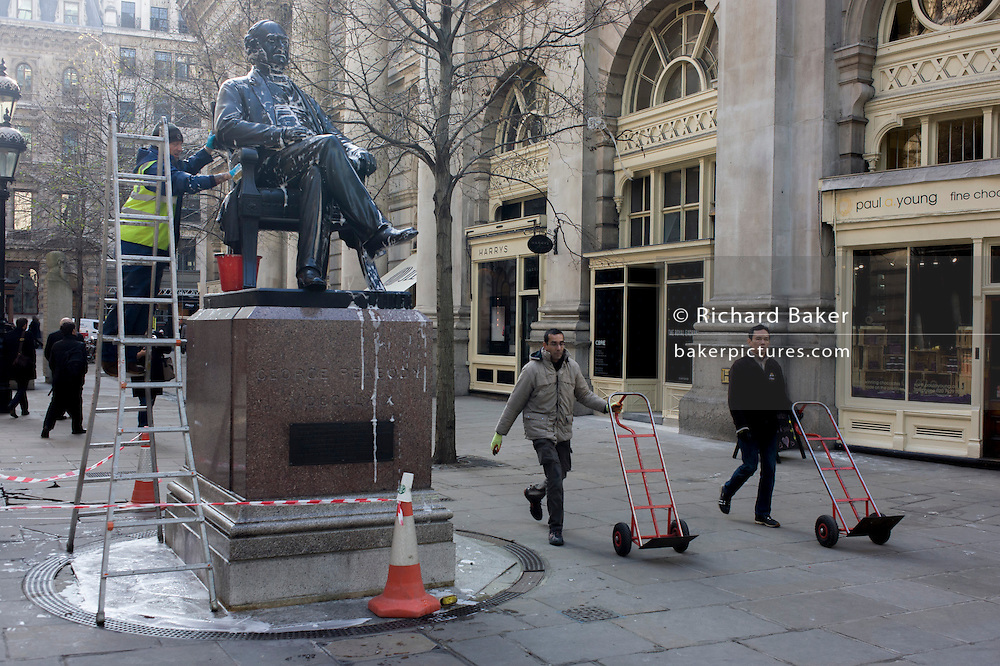 A conservator with City of London contractor Rupert Harris Conservation, washes off soap solution from the statue of Victorian philanthropist, entrepreneur and banker George Peabody (1795 to 1869). As part of a rolling programme of maintenance and cleaning by the Square Mile's governing Corporation, historic items - from statues and plaques to other pieces of historic value are regularly attended to.