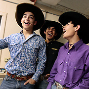 Gustavo Trevino, left, 17, cracks a joke about how much money he has earned riding bulls recently as Nathan Losoya, center, 16, and Arnold Guzman, right, 14, laughs while waiting to collect their prize money following a Texas Youth Rodeo Association event at the Sheriff's Posse Arena in Edinburg. Guzman placed first and Losoya second, winning $144 and $98. Trevino did not compete that night, but won $300 in an open rodeo at the same arena two weeks earlier. <br /> Nathan Lambrecht/The Monitor
