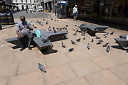People sitting in an area where feral pigeons gather on Oxford Street on 26th June 2020 in London, United Kingdom. Feral pigeons, also called city doves, city pigeons, or street pigeons, are pigeons that are derived from the domestic pigeons that have returned to the wild.