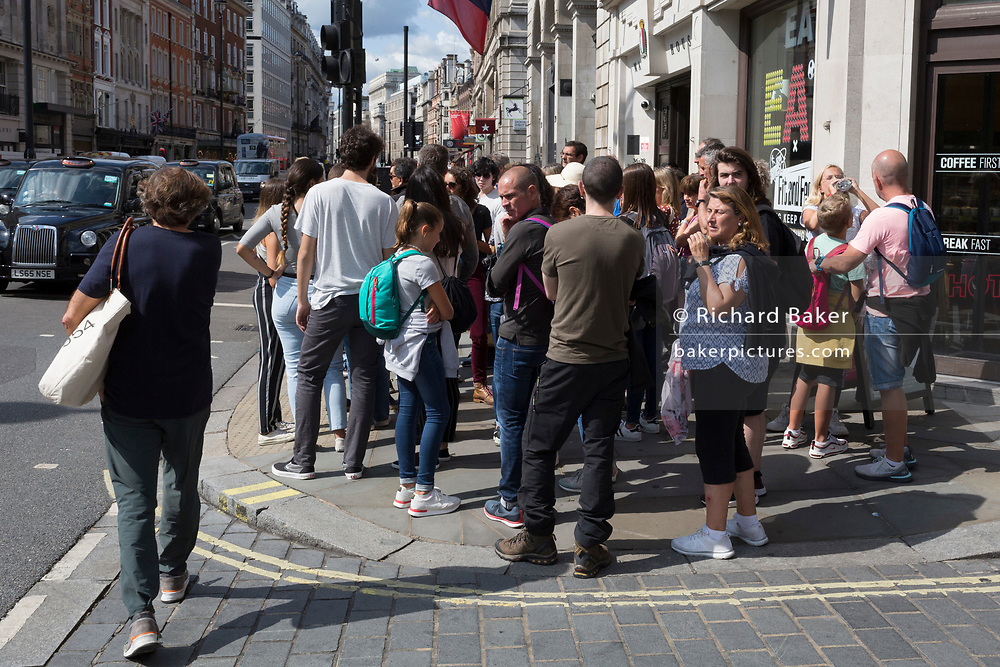 A group of Spanish tourists gather to listen to their tour guide, blocking the pavement on Piccadilly and forcing other pedestrians to walk out into on-coming traffic in order to pass, on 13th August 2019, in London England.