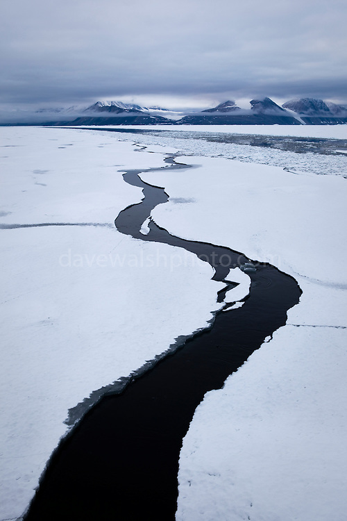 """A pathway opens in the landfast sea ice, forming a question mark in Dijmhna Sund, Nioghalvfjerdsfjorden, in Greenland's remote northeast corner. The Arctic Ocean sea ice continues to decline; as more white ice, which reflects sunlight back into space, is lost to due the burning of fossil fuels, the remaining dark water absorbs heat, creating a feedback effect spells bad news for the Arctic, and the global climate. Greenland, 2009<br /> <br /> This mage can be licensed via Millennium Images. Contact me for more details, or email mail@milim.com For giclée prints, contact me, or click """"add to cart"""" to some standard print options."""