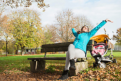 Mother stretching while sitting on bench in park by stroller