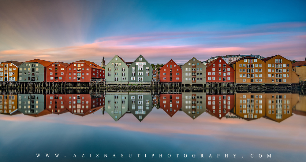 www.aziznasutiphotography.com              This picture has been taken around 11:40 pm in Trondheim Norway.              Trondheim with picturesque, tiny, wooden houses. This idyllic neighbourhood on the east side of the Nidelva river features old timber buildings, originally the homes of the working class. Now restored, Bakklandet is a charming mixture of houses, shops and cafés.<br /> Nidelva river cuts through the city, winding its way along the Nidarosdomen park and picturesque areas, with the historic, wooden wharf houses lining its sides towards the mouth at the Trondheim fjord, and the beautiful, wooden bridge amle Bybrocrossing the river.