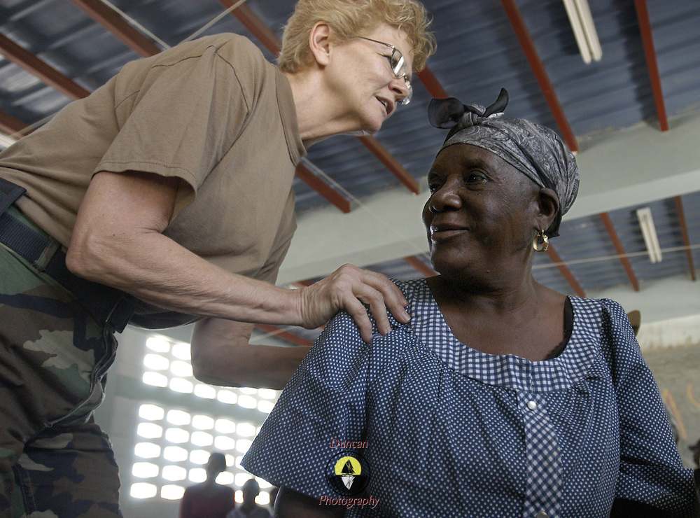 GONAIVES, Haiti (March 7, 2005) --  Navy Cmdr. Pat Phillips, left,  (a native of Columbus, Ohio) examines Francoise Castine, age 73, of Gonaives, at the Lycee Bicentenaire Universite in Gonaives.  Phillips is a reserve member of Fleet Hospital Great Lakes, out of Great Lakes, Ill. 'Once a nurse, always a nurse,' Phillips said. Besides serving as a nurse in the Navy, and in her full-time job as a civilian, she took a 2-week trip to Haiti in November with a medical mission group to do nursing work. She and her teammates from Fleet Hospital are now contributing to New Horizons, a three-month humanitarian and civic assistance exercise in Haiti sponsored by Commander U.S. Southern Command.  The Task Force conducting New Horizons will build three school houses, drill three potable water wells and conduct free health clinics.  U.S. Navy photo by Photographer's Mate 2nd Class Roger S. Duncan, Fleet Combat Camera, Atlantic.