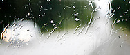 A rainy day on the road with focus on the water streaming across the windshield and out of focus lights of an oncoming vehicle - panorama