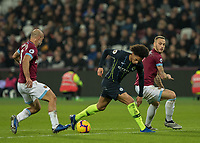 Football - 2018 / 2019 Premier League - West Ham United vs. Manchester City<br /> <br /> Leroy Sane (Manchester City) gets the ball caught under his feet as he tries to go through the middle of Marko Arnautovic (West Ham United) and Pablo Zabaleta (West Ham United) at the London Stadium<br /> <br /> COLORSPORT/DANIEL BEARHAM