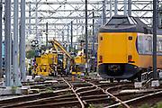 Een intercity passeert bij het verlaten van Utrecht CS de werkzaamheden aan het spoor. In Utrecht vindt het treinverkeer veel hinder van de werkzaamheden. Van 9 augustus tot en met 17 augustus 2014 wordt aan het spoor gewerkt. Doel is om het aantal wissels sterk te verminderen, waardoor er een betere doorstroming van het treinverkeer is, minder kans op vertragingen en een hoger comfort voor de reizigers. Door de vernieuwing van het spoorwegemplacement kunnen meer treinen het station aandoen. De werkzaamheden zullen tot en met 2016 duren en vinden vooral 's nachts, in het weekend en de vakanties plaats. Daarna moet het belangrijkste spoorwegknooppunt van Nederland weer optimaal functioneren.<br /> <br /> In Utrecht the trains have lots of detours due to construction work. From August 9 to August 17, 2014 ProRail is working on the track. The aim is to reduce the junctions, creating a better traffic flow with less chance of delays and greater comfort for the passengers. Greatly the number of switches is reduced. The work will continue through 2016 and takes especially at night, weekends and holidays place. After that, the most important railway junction in the Netherlands must function optimally again.