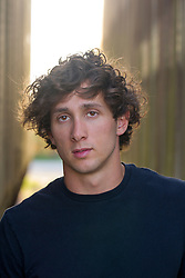 good looking  young man with curly brown hair wearing a black tee shirt