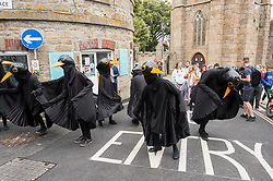 © Licensed to London News Pictures; 11/06/2021; St Ives, Cornwall UK. G7 summit in Cornwall. Performers dressed as blackbirds dance at a protest by Extinction Rebellion processes through the streets of St Ives on the first day of the G7 summit. Photo credit: Simon Chapman/LNP.