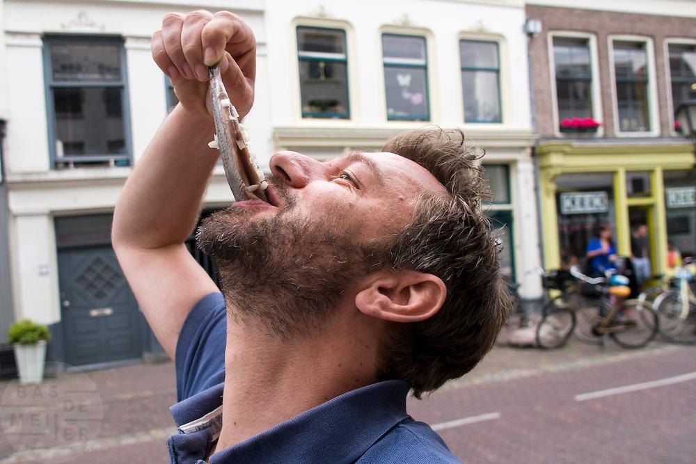 In Utrecht eet een man een Hollandse Nieuwe met uitjes op straat.<br /> <br /> In Utrecht a man is eating a raw herring with onions.<br /> Foto Bas de Meijer / Hollandse Hoogte