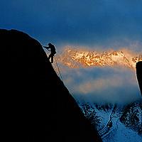 A rock climber rappels off of a boulder in Buttermilk Rocks.