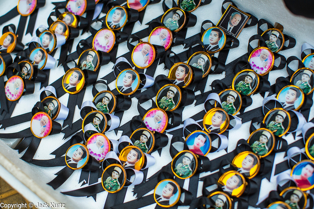 """29 JANUARY 2013 - PHNOM PENH, CAMBODIA:  Pins of Norodom Sihanouk for sale to mourners in front of the palace in Phnom Penh, Cambodia. Sihanouk (31 October 1922- 15 October 2012) was the King of Cambodia from 1941 to 1955 and again from 1993 to 2004. He was the effective ruler of Cambodia from 1953 to 1970. After his second abdication in 2004, he was given the honorific of """"The King-Father of Cambodia."""" Sihanouk held so many positions since 1941 that the Guinness Book of World Records identifies him as the politician who has served the world's greatest variety of political offices. These included two terms as king, two as sovereign prince, one as president, two as prime minister, as well as numerous positions as leader of various governments-in-exile. He served as puppet head of state for the Khmer Rouge government in 1975-1976. Most of these positions were only honorific, including the last position as constitutional king of Cambodia. Sihanouk's actual period of effective rule over Cambodia was from 9 November 1953, when Cambodia gained its independence from France, until 18 March 1970, when General Lon Nol and the National Assembly deposed him. Upon his final abdication, the Cambodian throne council appointed Norodom Sihamoni, one of Sihanouk's sons, as the new king. Sihanouk died in Beijing, China, where he was receiving medical care, on Oct. 15, 2012. His cremation is scheduled to take place on Feb. 4, 2013. Over a million people are expected to attend the service.      PHOTO BY JACK KURTZ"""