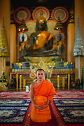 A Buddhist monk wearing saffron robes kneeling on the floor of the temple in front of a large, bronze statue (The Phra Ong Teu), Wat Ong Teu, Vientiane, Laos