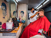 """06 FEBRUARY 2017 - BANGKOK, THAILAND: A barber cuts a customer's hair in a small barbershop in what used to be known as Kalabok Market under the Phra Khanong Bridge in the Phra Khanong district of Bangkok. Kalabok is the Thai word for hairdresser and the market was called Kalabok because there were many barbershops and hairdressers under the bridge. In 1985, the city changed the name of the market to """"Singha Market."""" There are still about 10 small men's barbershops, most with just one barber, and four women's salons, most with one hairdresser,  under the bridge.      PHOTO BY JACK KURTZ"""