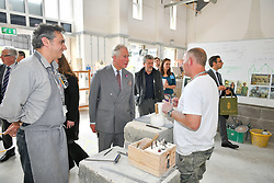 The Prince of Wales meets stone masons Peter Loizou (left) and Edward Ramsbottom (right) during a visit to Weymouth College on Middle Farm Way, in Poundbury, Dorchester, to meet stone masonry students and view their work.