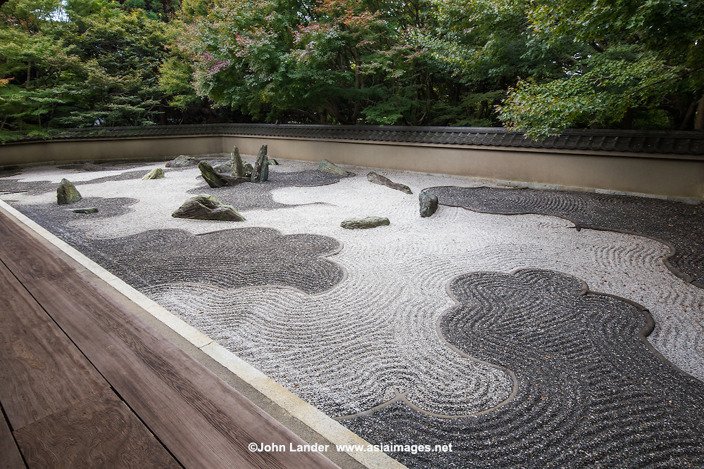 """Ryogin-an was originally the residence of the third abott of Tofuku-ji. The Garden of the Dragon is one of the finest modern karesansui gardens designed by Shigemori Mirei, with stones dramatically placed amidst black and white gravel - each dark area represents a dragon or clouds.  The Eastern garden is the """"Garden of the Inseparable"""", with a simple ginkgo tree standing in the background. This garden uses purple gravel that is not common for zen gardens, and hints at the recency of its design. All three gardens were designed by Shigemori Mirei a modern master landscape gardener who designed other gardens in Tofukuji as well as others in Kyoto and indeed Japan."""