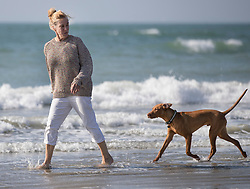 © Licensed to London News Pictures. 10/10/2018. West Wittering, UK. Wendy splashes in the sea with her Hungarian Vizsla Bean at West Wittering as unseasonably high temperatures hit parts of the UK. Photo credit: Peter Macdiarmid/LNP