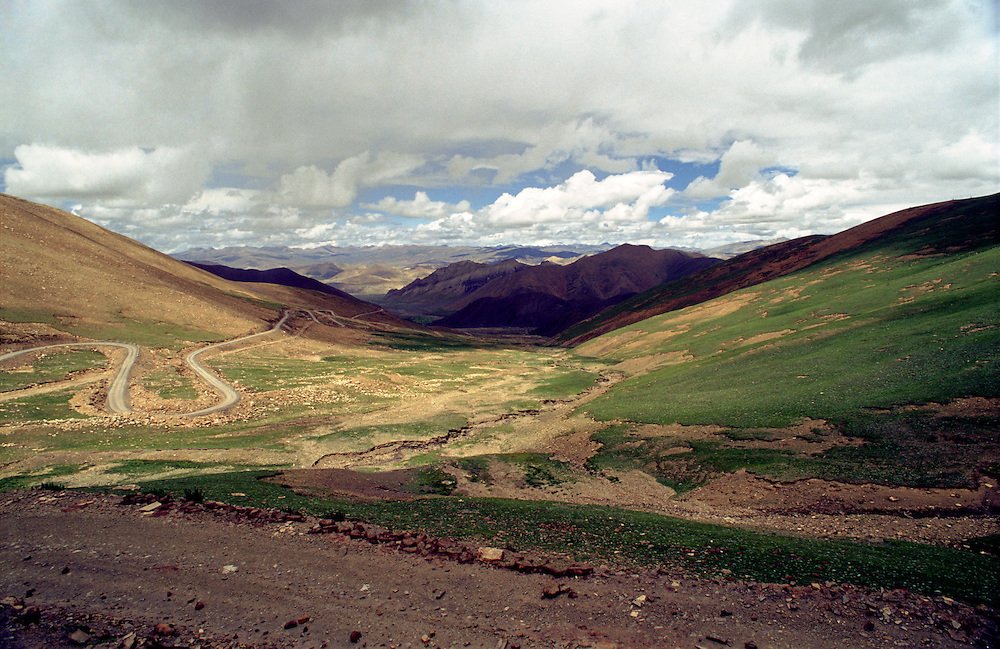 A road weaves through a valley in the Tibetan countryside, Tibet.