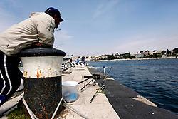 Questo pescatore occasionale, fotografato nel porto di Brindisi, si sta godendo il fine settimana dedicandosi al suo passatempo preferito. Nei primi mesi di giugno, quando le acque si riscaldano, le orate si avvicinano verso le banchine del porto per cibarsi di grossi molluschi presenti appunto sulle pareti delle banchine.