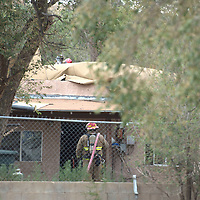 McKinley County firefighters secure a house on the North side of Gallup Wednesday after an accident exploded the roof off the house.