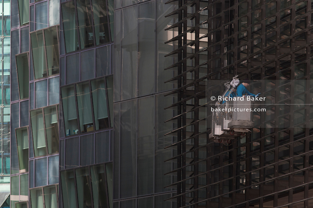 Two window cleaners work from the safety of a hanging cradle as they clean the glass of an office complex in the City of London, the capital's financial district - also known as the Square Mile. Working as a pair of contractors, the men clean methodically - progressing downwards on each area of glass. The City of London is the capital's historic centre first occupied by the Romans then expanded during following centuries until today, it has a resident population of under 10,000 but a daily working population of 311,000.