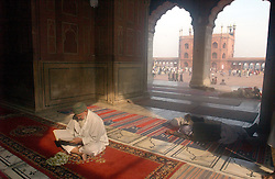 A Muslim reads the Koran inside the Jamia Masjid, or Grand Mosque, the first day of the Muslim Eid al-Fitr holiday marking the end of the holy month of Ramadan in Delhi, India December 17, 2001.  (Getty Images/ Ami Vitale)