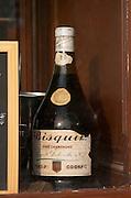 Restaurant. Old bottle of Bisquit cognac in the window. Bordeaux city, Aquitaine, Gironde, France