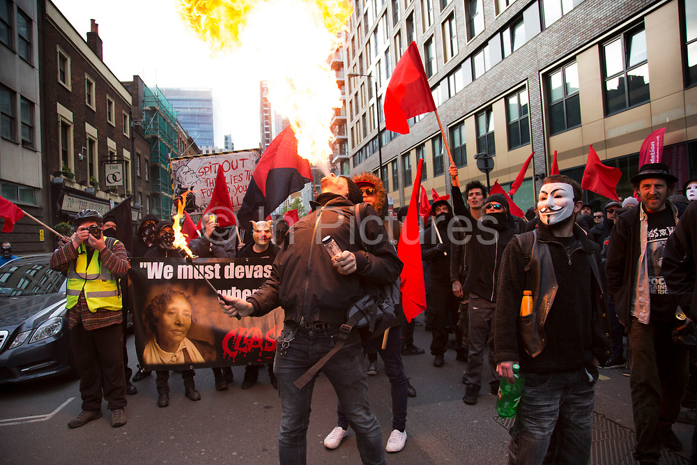 Anarchists gather as a black bloc for the Fuck Parade to party and protest at the class and wealth divide between rich and poor and the gentrification of London, the demonstration was organised by anarchist group Class War on May 1st 2016 in London, United Kingdom. The parade is now part of the May Day activism calendar as dissatisfaction about the establishment, the police and the inadequacy of the press is highlighted. A fire breather shoots up a flame at the protest gathers in the City.