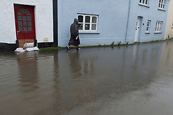 © Licensed to London News Pictures. 26/10/2019. Crickhowell, Powys, Wales, UK. A pedestrian walks through flood water in Bridge Sytreet in Crickhowell, Powys as rain falls relentlessly and the level of the river Usk rises dramatically. Water enters The Bridge End Inn basement in Bridge Street, Crickhowell  in Powys. Photo credit: Graham M. Lawrence/LNP