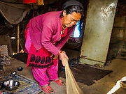 04 MARCH 2017 - KATHMANDU, NEPAL: A woman from rural Nepal cleans her tent in an IDP camp in the center of Kathmandu. Her husband found work on a chicken farm about 90 minutes from Kathmandu and lives at the farm, coming back to the camp one night a week. The camp opened days after the April 2015 earthquake devastated Nepal, killing almost 9,000 people. At its peak, about 1,800 families lived in the camp. The camp is still open nearly two years after the earthquake, about 400 families currently live in the camp. Camp residents say the Kathmandu municipal government is trying to close the camp and is encouraging residents to find new housing. They said the government is cutting off services to the camp and last week stopped the free distribution of water, although water can be purchased for delivery. Most of the people in the camp came to Kathmandu from rural villages in the mountains in the weeks after the earthquake. Many of the residents of the camp, technically homeless, have found work in Kathmandu's bustling construction industry, rebuilding homes destroyed in the earthquake.       PHOTO BY JACK KURTZ
